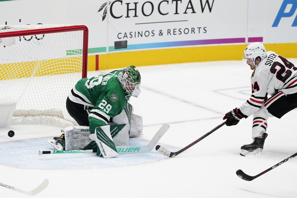 Dallas Stars goaltender Jake Oettinger (29) is unable to stop a shot by Chicago Blackhawks' Pius Suter (24) in overtime of an NHL hockey game in Dalla...