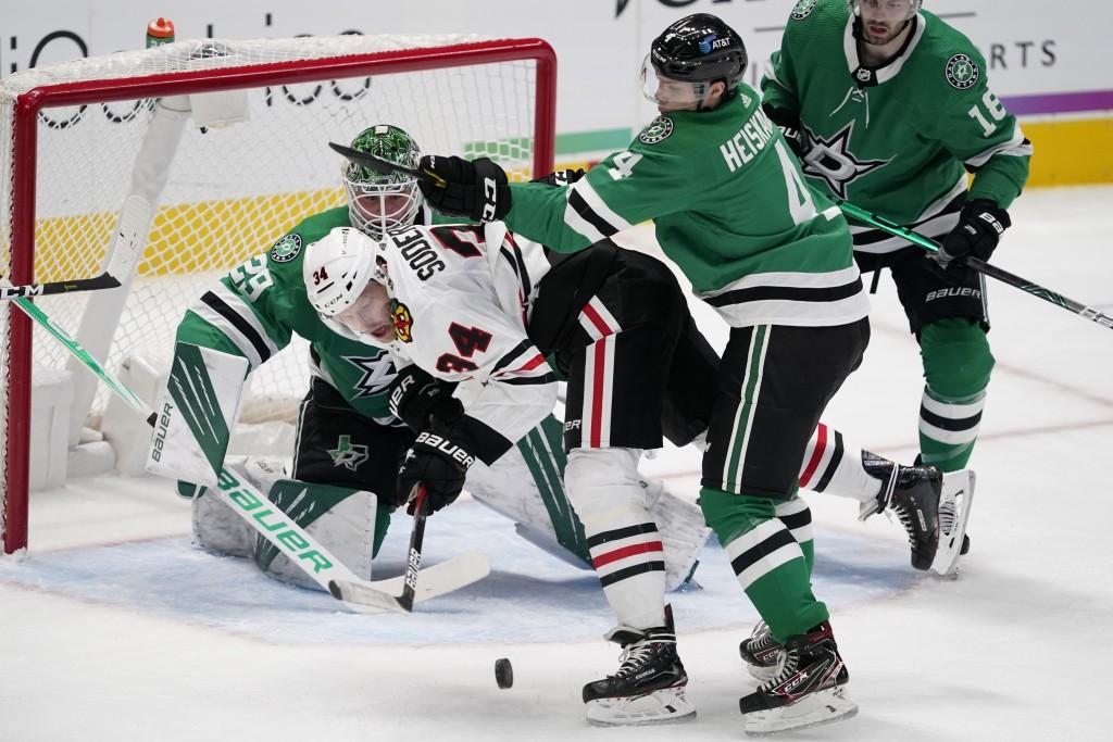Chicago Blackhawks center Carl Soderberg (34) is unable to take a shot as Dallas Stars' Miro Heiskanen (4) and Jason Dickinson (18) help goalie Jake O...