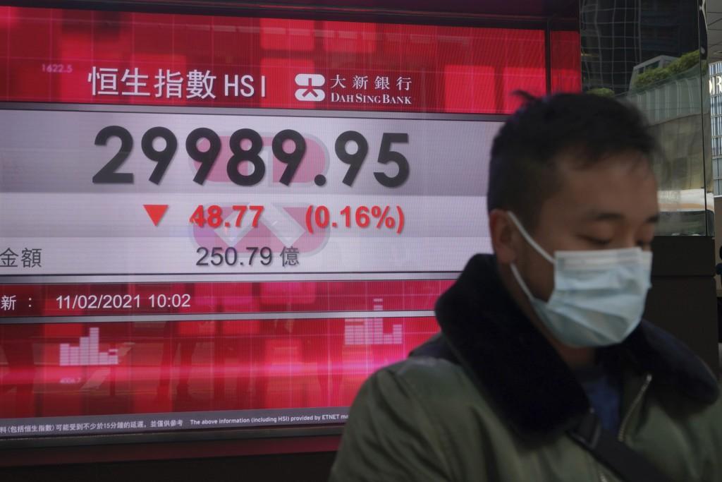 A man wearing a face mask walks past a bank's electronic board showing the Hong Kong share index in Hong Kong, Thursday, Feb. 11, 2021. Despite a shor...