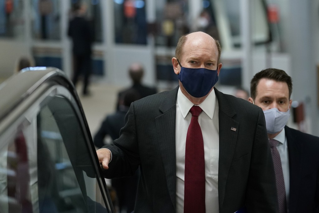 Sen. Chris Coons, D-Del., rides an escalator on Capitol Hill in Washington, Wednesday, Feb. 10, 2021, as he heads to the second day of the second impe...