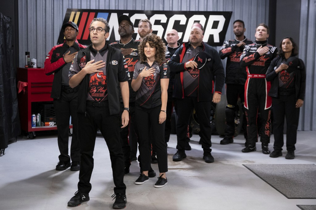 This image released by Netflix shows Dan Ahdoot, foreground, Kevin James, fourth from right and Freddie Stroma, second right, in a scene from the come...