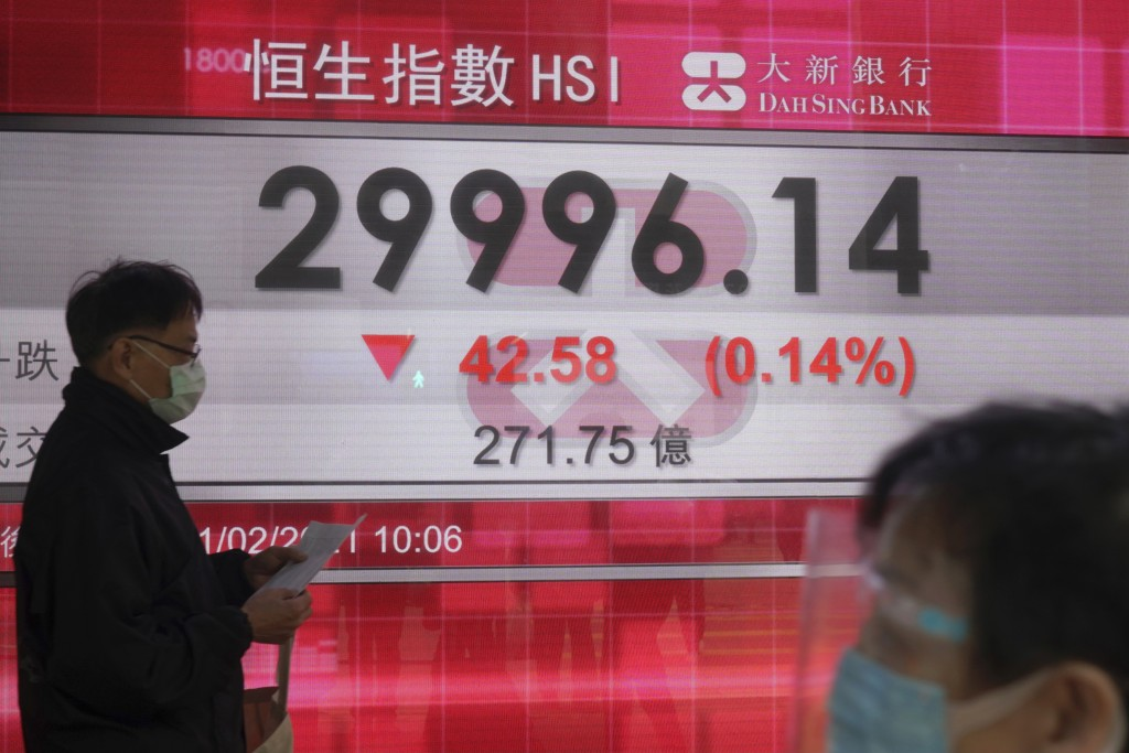 People wearing a face masks walk past a bank's electronic board showing the Hong Kong share index in Hong Kong, Thursday, Feb. 11, 2021. Despite a sho...