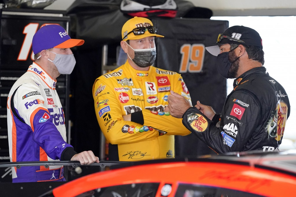 Denny Hamlin, left, Kyle Busch, center and Martin Truex Jr. talk in a garage before the start of a NASCAR Daytona 500 auto race practice session at Da...