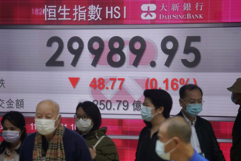 People wearing face masks walk past a bank's electronic board showing the Hong Kong share index in Hong Kong, Thursday, Feb. 11, 2021. Despite a short...