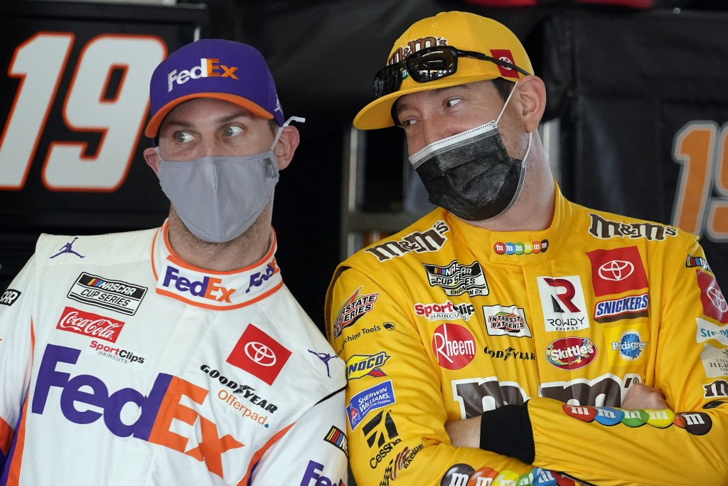Denny Hamlin, left, and Kyle Busch joke around in the garages during a NASCAR Daytona 500 auto race practice session at Daytona International Speedway...