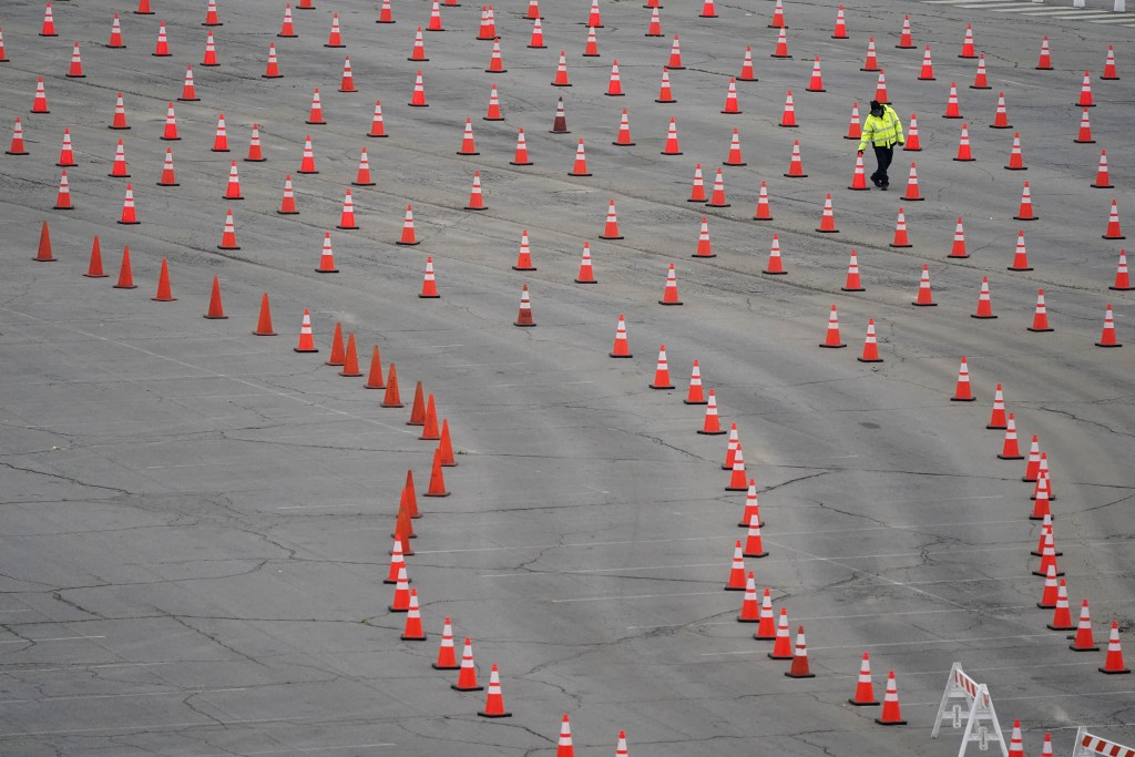 A worker arranges cones at a mostly-empty vaccination site at Dodger Stadium, Thursday, Feb. 11, 2021, in Los Angeles. A nationwide shortage of COVID-...