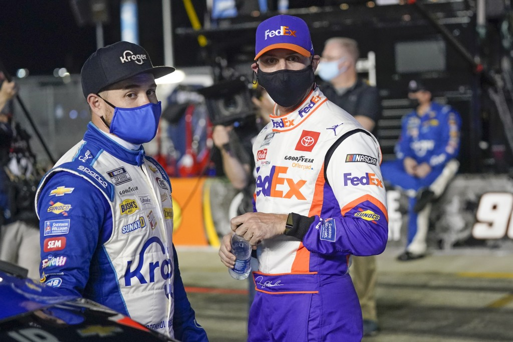 Ricky Stenhouse Jr., left, and Denny Hamlin talks on pit road before the first of two qualifying NASCAR auto races for the Daytona 500 at Daytona Inte...