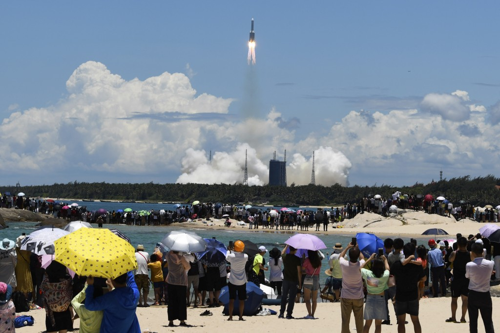 In this July 23, 2020, file photo released by China's Xinhua News Agency, spectators watch as a Long March-5 rocket carrying the Tianwen-1 Mars probe ...