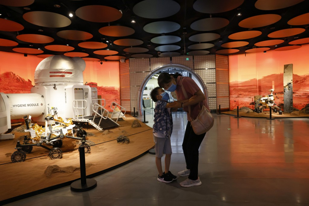In this July 23, 2020, file photo, a child whispers to a woman as they visit an exhibition depicting Mars rovers and bio-domes in Beijing. China is fa...
