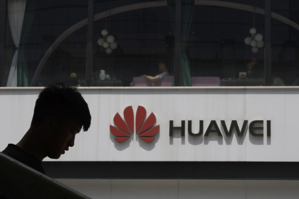 FILE - In this Thursday, May 16, 2019 file photo, a man is silhouetted near the Huawei logo in Beijing. Huawei took U.K. bank HSBC to court on Friday,...