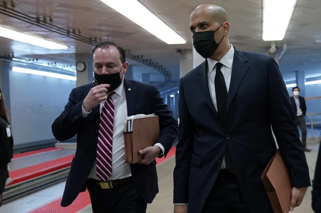 Sen. Mike Lee, R-Utah, left, and Sen. Cory Booker, D-N.J., right, walk on Capitol Hill in Washington, Thursday, Feb. 11, 2021, before the start of the...
