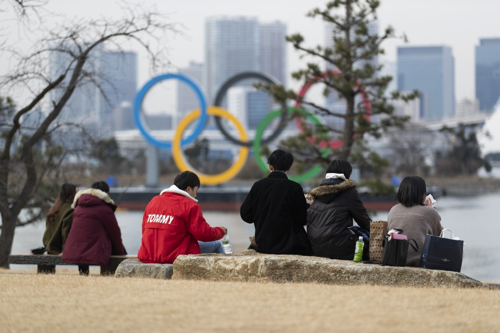 People have lunch at the Odaiba Marine Park where a statue of the Olympic rings is displayed in Tokyo on Friday, Feb. 12, 2021. (AP Photo/Hiro Komae)
