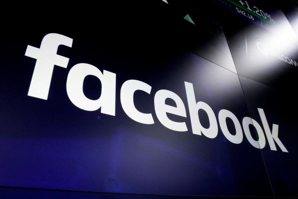 FILE - In this March 29, 2018, file photo, the Facebook logo on a screen at Nasdaq in Time Square, New York. Australia's Parliament will debate making...