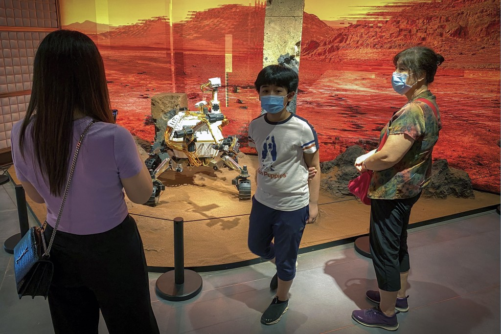 In this July 20, 2020, file photo, shoppers wearing face masks to protect against the spread of the coronavirus look at a replica of a Mars rover on d...
