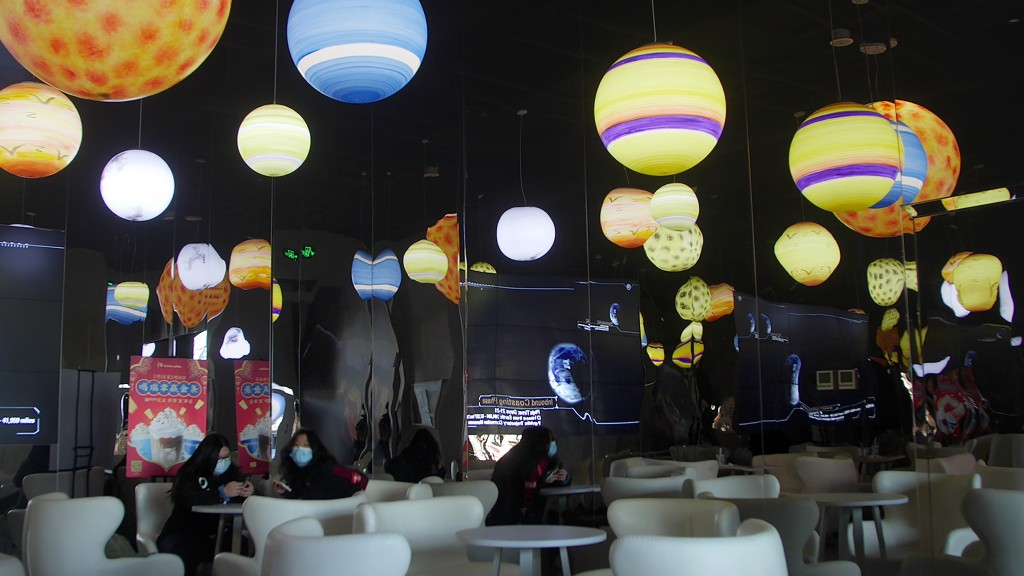Customers sit beneath lighted globes representing the different planets of the solar system at a space-themed cafe in Beijing, Wednesday, Feb. 10, 202...