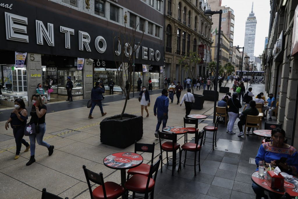 Diners eat at tables on the pedestrian walkway Madero, where temporary pandemic rules have allowed street tables and retail displays, in central Mexic...
