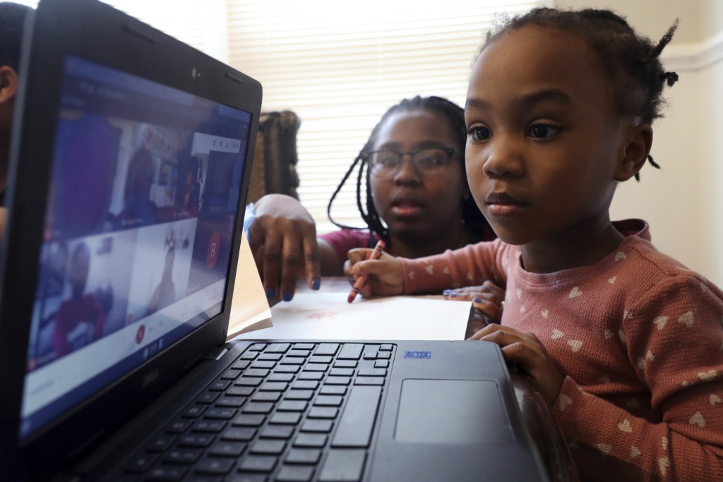 FILE - In this Feb. 10, 2021, file photo, Lear Preston, 4, who attends Scott Joplin Elementary School, participates in her virtual classes as her moth...