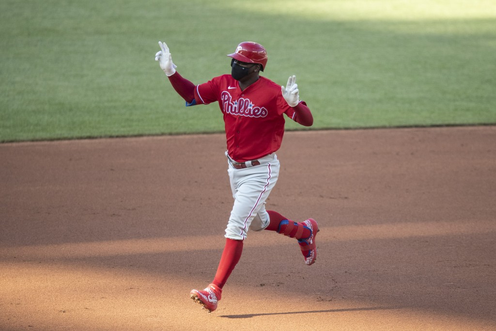 FILE - Philadelphia Phillies' Didi Gregorius celebrates as he rounds the bases for his three-run homer during the first inning of an exhibition baseba...