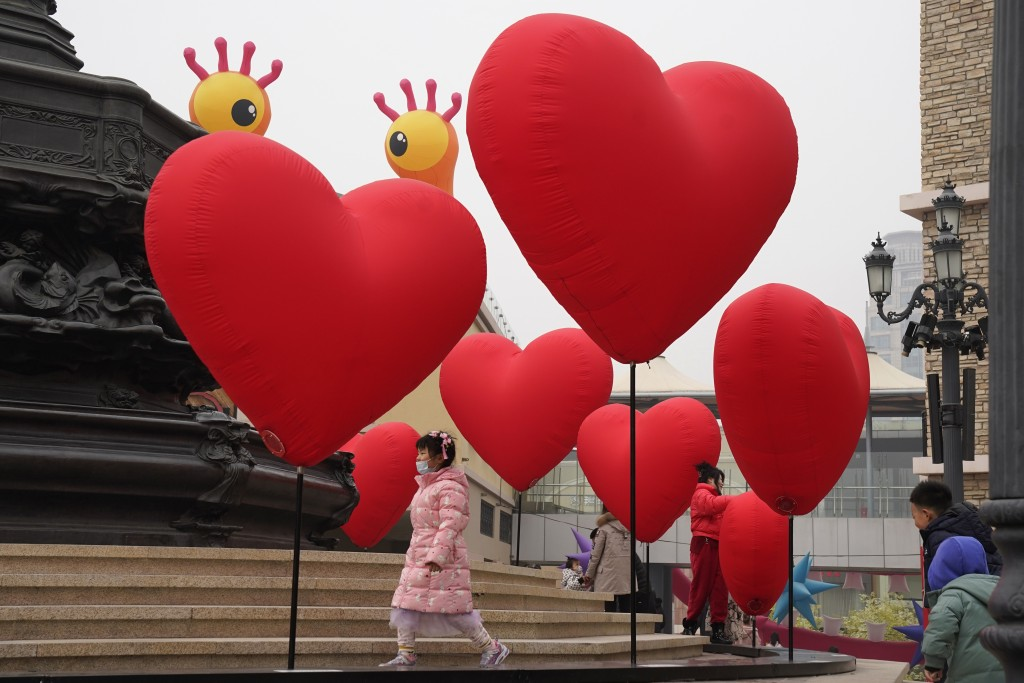 Visitors wearing a mask to protect from the coronavirus stand near heart shaped balloons displayed at a mall district during the second day of the Chi...