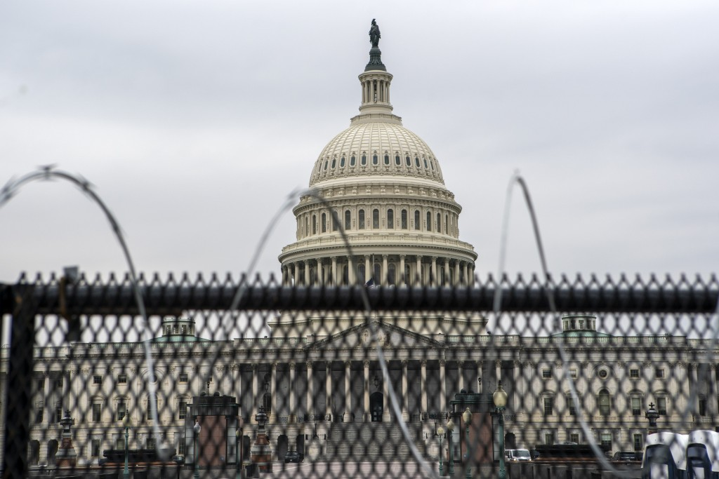 The U.S. Capitol is seen through a fence with barbed wire during the second impeachment trial of former President Donald Trump in Washington, Friday, ...