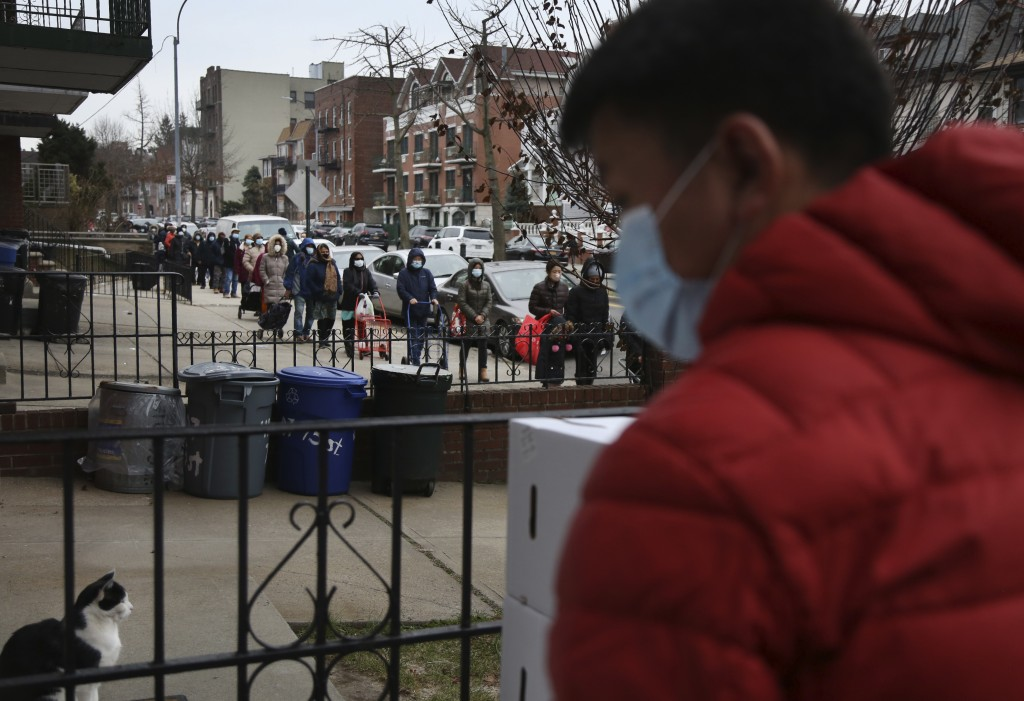 A line of people stretches for two blocks outside the United Sherpa Association's weekly food pantry on Friday, Jan. 15, 2021, in the Queens borough o...