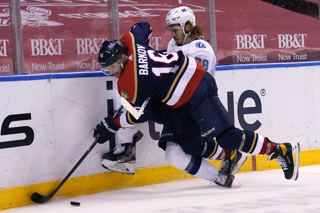 Florida Panthers center Aleksander Barkov (16) and Tampa Bay Lightning defenseman Mikhail Sergachev (98) go for the puck during the second period of a...