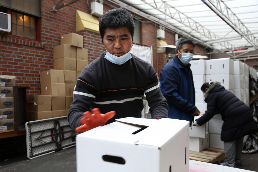 Phurba Sherpa, left, and other volunteers move boxes of food at the United Sherpa Association's weekly food pantry on Friday, Jan. 15, 2021, in the Qu...