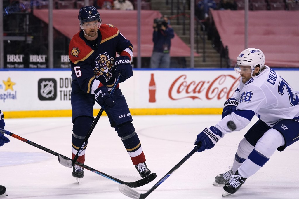 Tampa Bay Lightning center Blake Coleman (20) and Florida Panthers defenseman Anton Stralman (6) go for the puck during the third period of an NHL hoc...