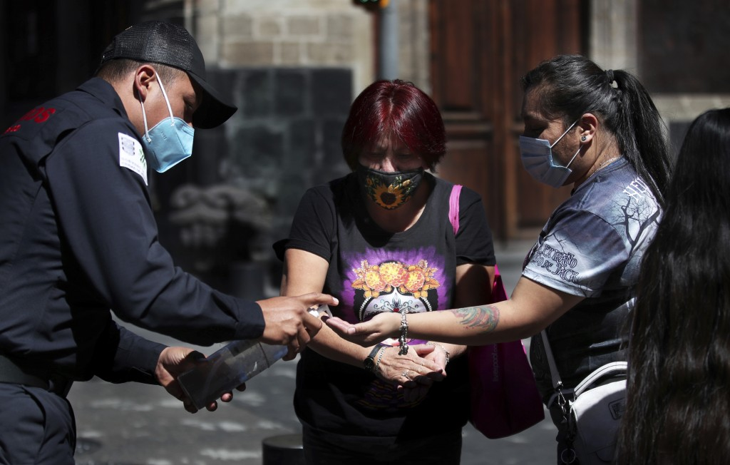 A firefighter gives disinfectant gel to women out shopping after authorities changed the health alert to orange after weeks in red, in Mexico City, Sa...