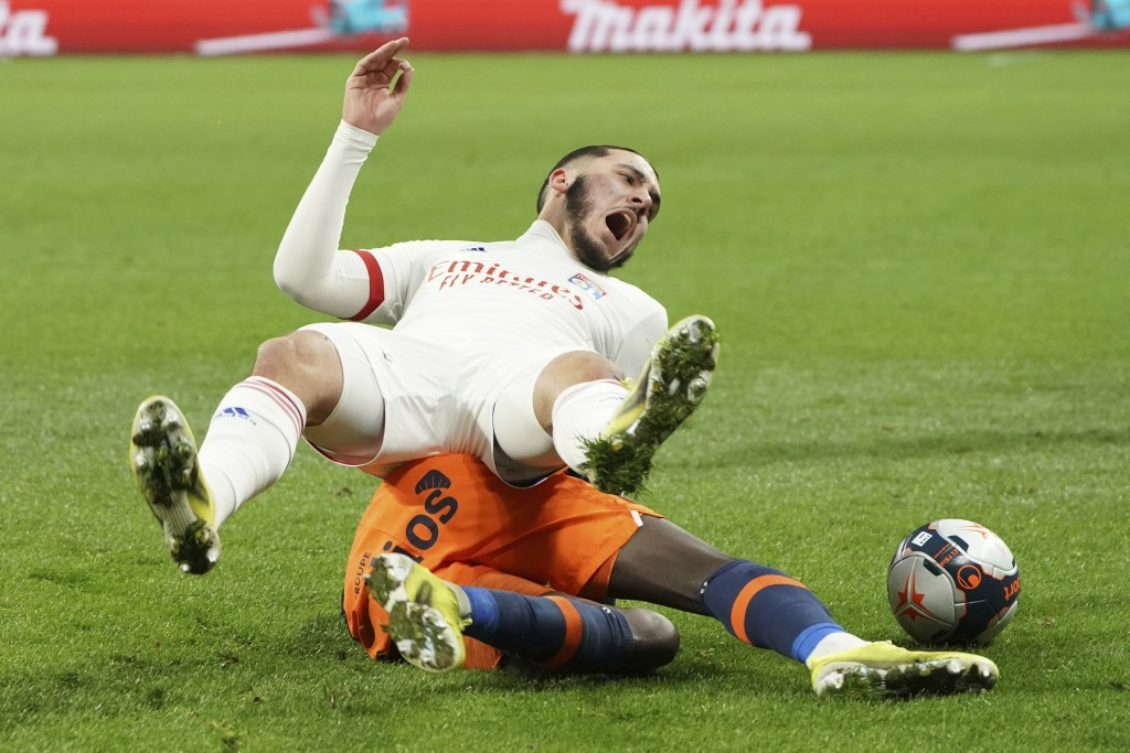 Lyon's Rayan Cherki, top, and Montpellier's Junior Sambia fight for the ball during the French League One soccer match between Lyon and Montpellier in...