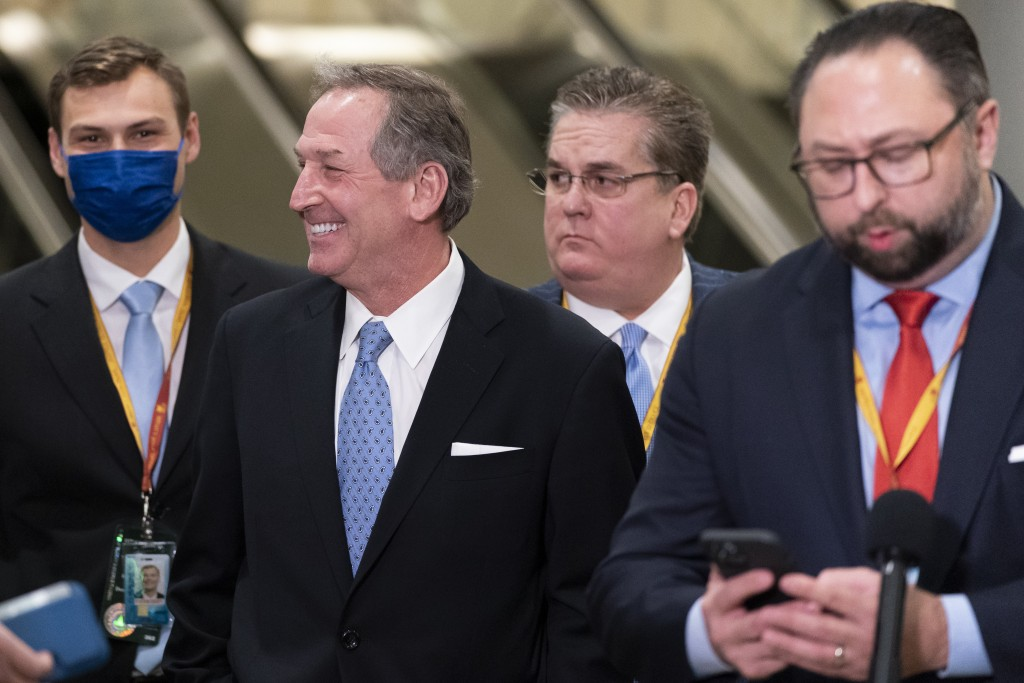 Michael van der Veen, second from left, an attorney from former President Donald Trump, smiles at reporters on Capitol Hill after the Senate acquitted...