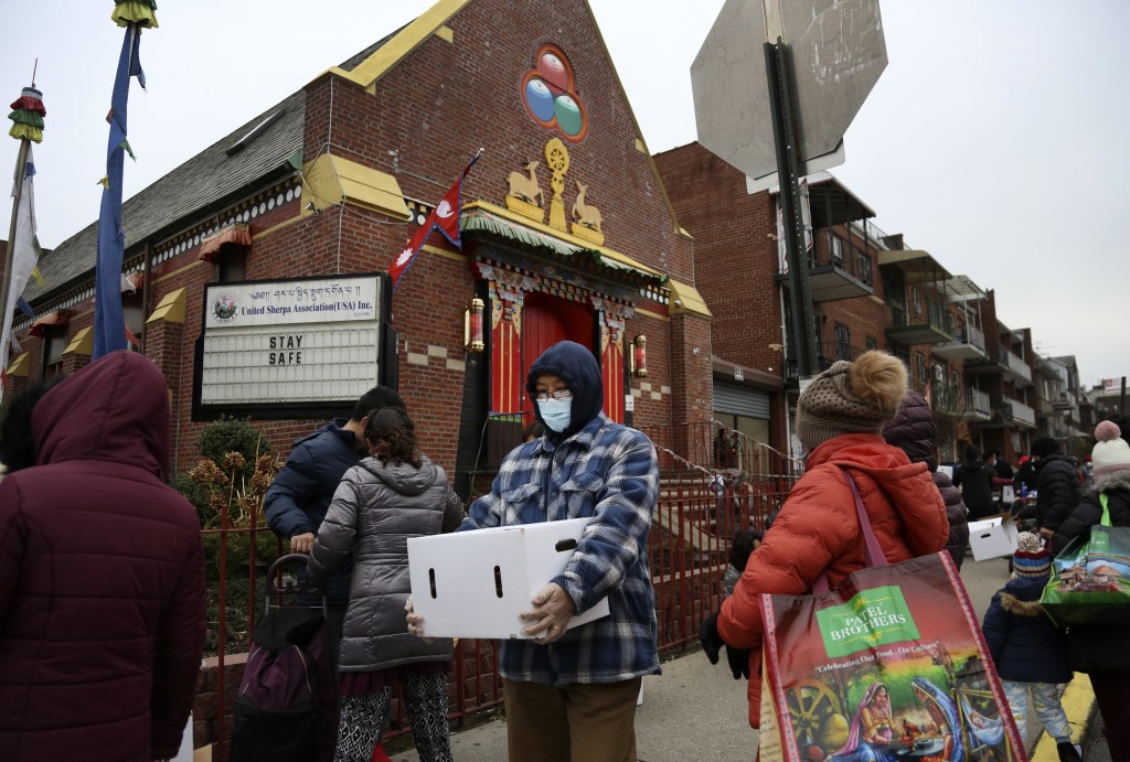 People receive free food from the United Sherpa Association's weekly food pantry on Friday, Jan. 15, 2021, in the Queens borough of New York. The pant...