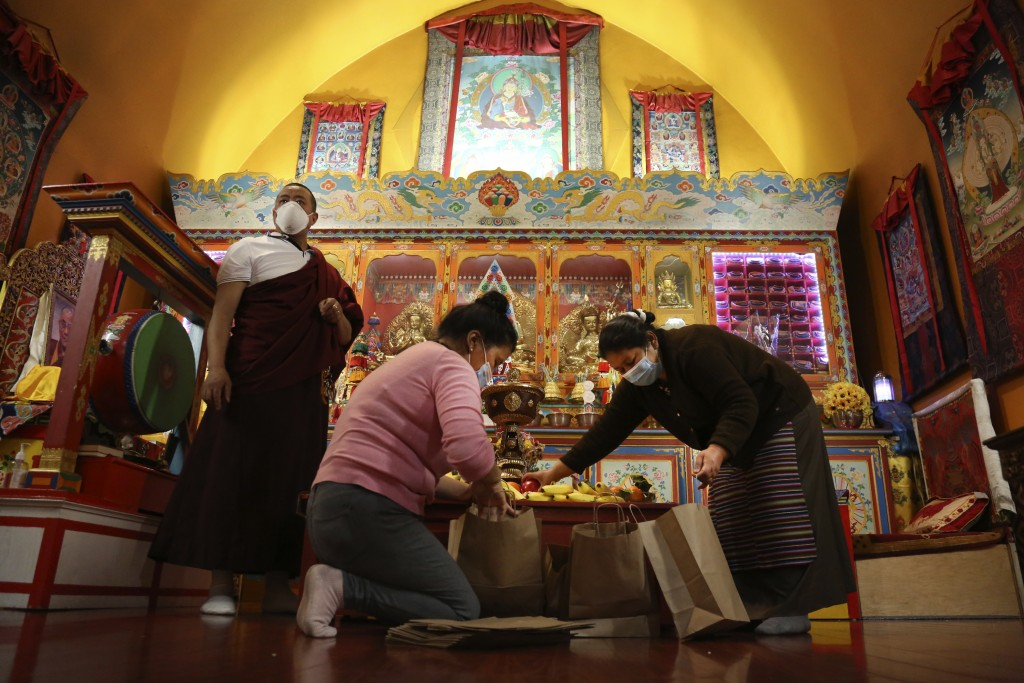 Lama Gelbu, left, Pasang Sherpa, center, and Yanddu Lama, right, prepare bags of fruit used as ceremonial offerings at the conclusion of the Dakini Da...