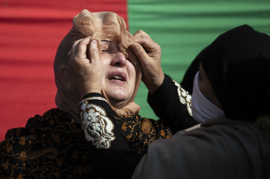 A woman wipes the tears of one the family members of Basharat Ahmad Zargar during his funeral in Srinagar, Indian-controlled Kashmir, Sunday, Feb.14, ...