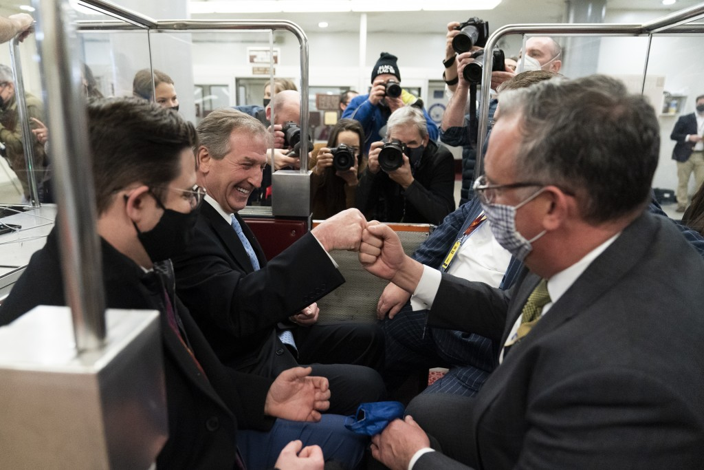 Michael van der Veen, second from left an attorney for former President Donald Trump, fist bumps a colleague as the depart on the Senate Subway, on Ca...