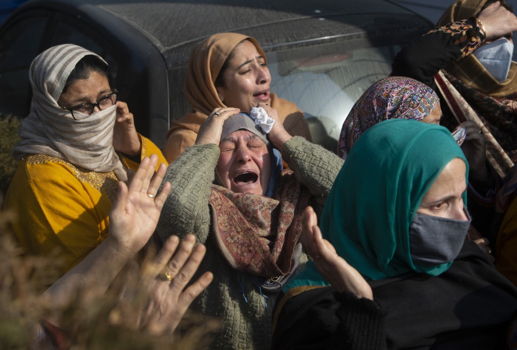 Relatives of Basharat Ahmad Zargar cry during his funeral in Srinagar, Indian-controlled Kashmir, Sunday, Feb.14, 2021. Zargar, who was working at a p...