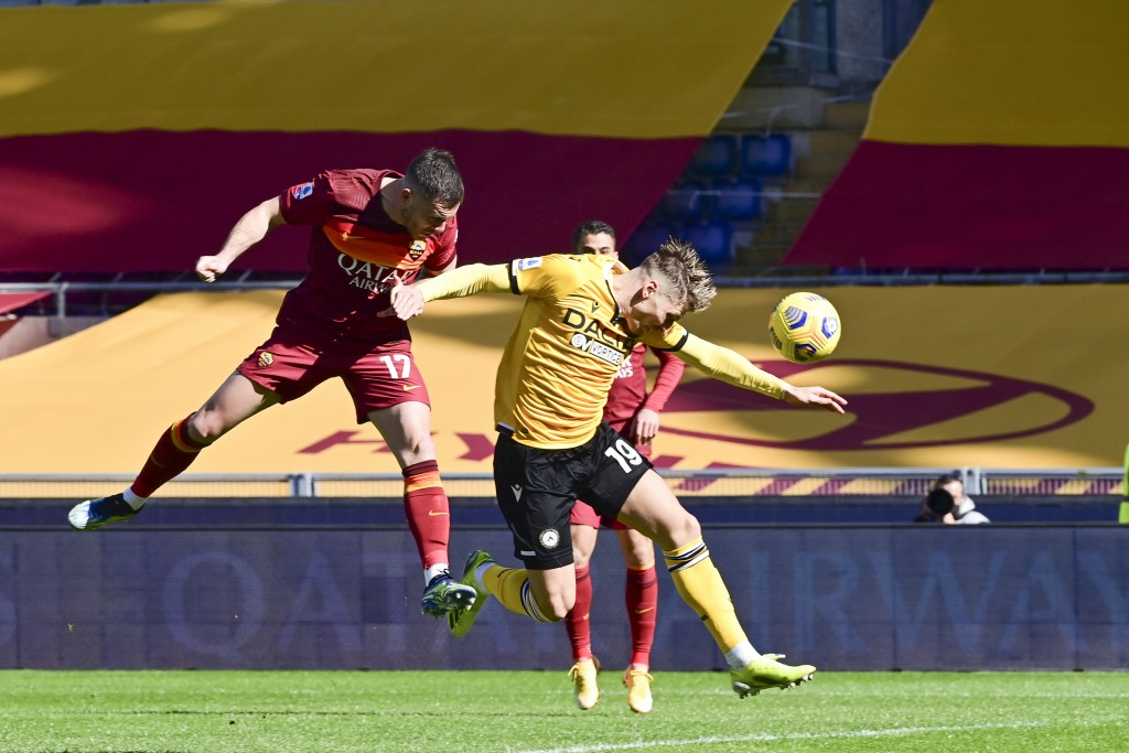 Roma's Jordan Veretout , left, scores his side's first goal during a Serie A soccer match between Roma and Udinese, at Rome's Olympic stadium, Sunday,...