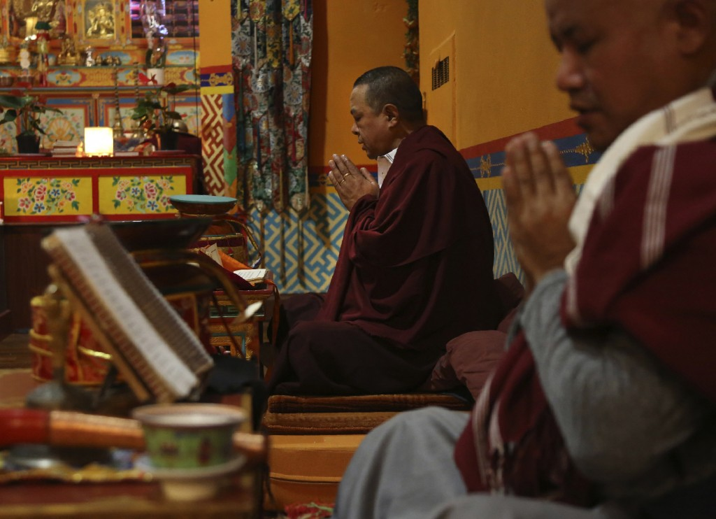 Lama Gelbu, left, and Pasang Sherpa, right, partake in the traditional Buddhist Dakini Day practice, a group meditationthat includessong and foodan...