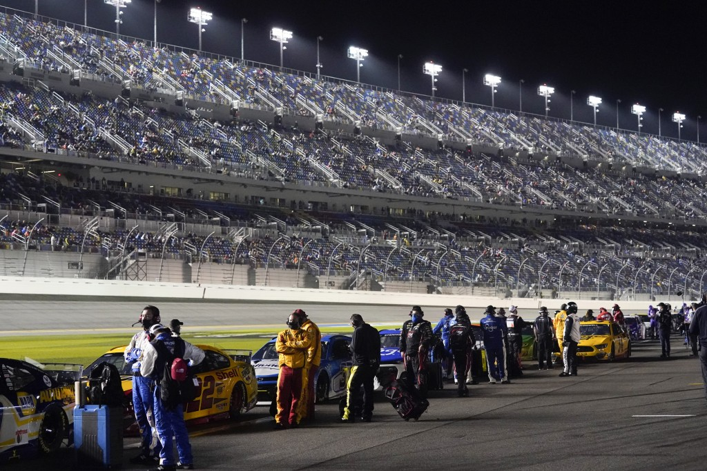 Drivers return to their cars after a weather delay during the NASCAR Daytona 500 auto race at Daytona International Speedway, Sunday, Feb. 14, 2021, i...