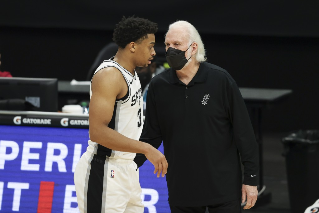 San Antonio Spurs coach Gregg Popovich, right, talks to San Antonio Spurs forward Keldon Johnson during the second half of an NBA basketball game agai...