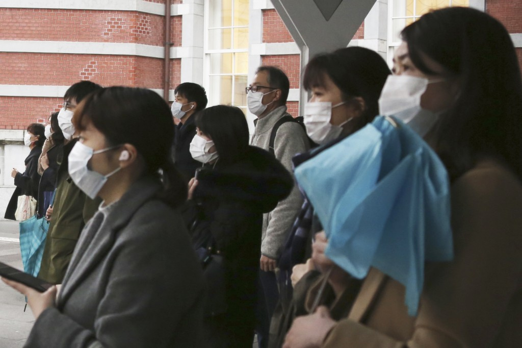 People wearing face masks to protect against the spread of the coronavirus wait for signals to turn to green at a crossing in Tokyo, Monday, Feb. 15, ...