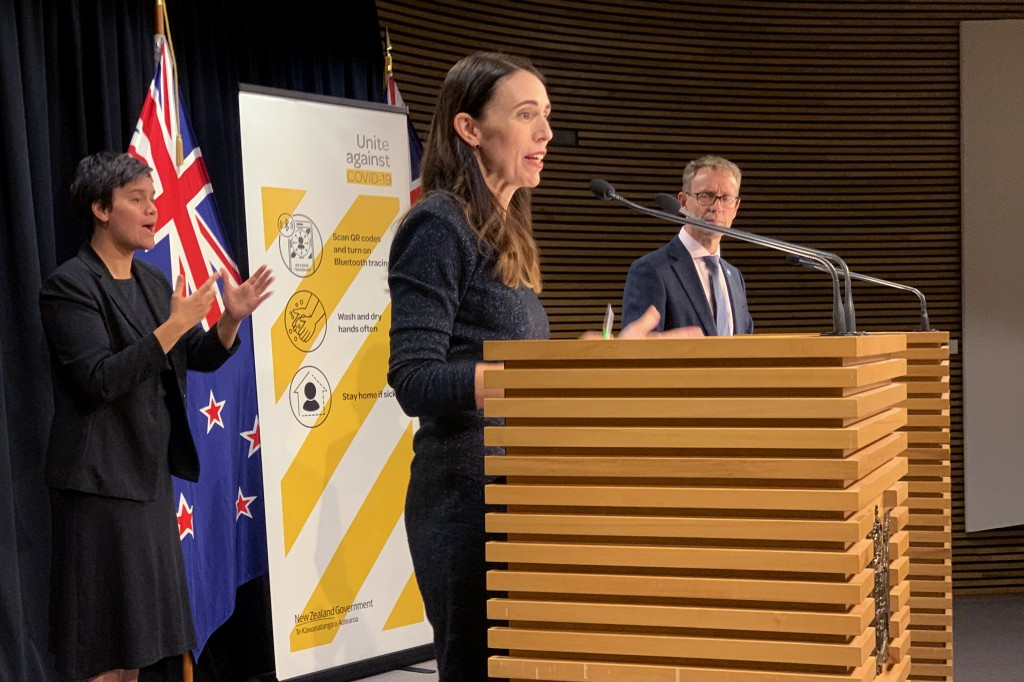 New Zealand's Prime Minister Jacinda Ardern, center, and Director-General of Health Ashley Bloomfield, right, talk to media in Wellington, New Zealand...