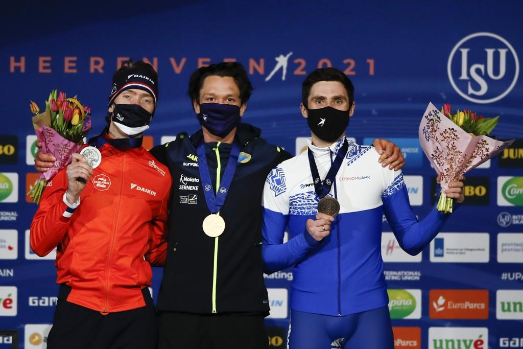 New world champion Sweden's Nils van der Poel, center and gold medal, Netherlands' Jorrit Bergsma, left and silver medal, and Russian skater Alexander...