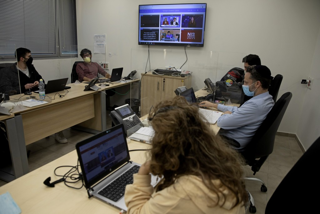 """People work at a digital task force to counter """"fake news"""" on the Internet, in the Health Ministry office near Tel Aviv, Israel, Sunday, Feb. 14, 2021..."""