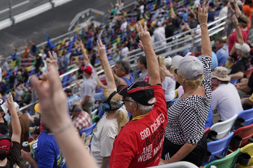 Fans hold up three fingers during a lap three tribute honoring the late Dale Earnhardt, Sr., during the NASCAR Daytona 500 auto race at Daytona Intern...