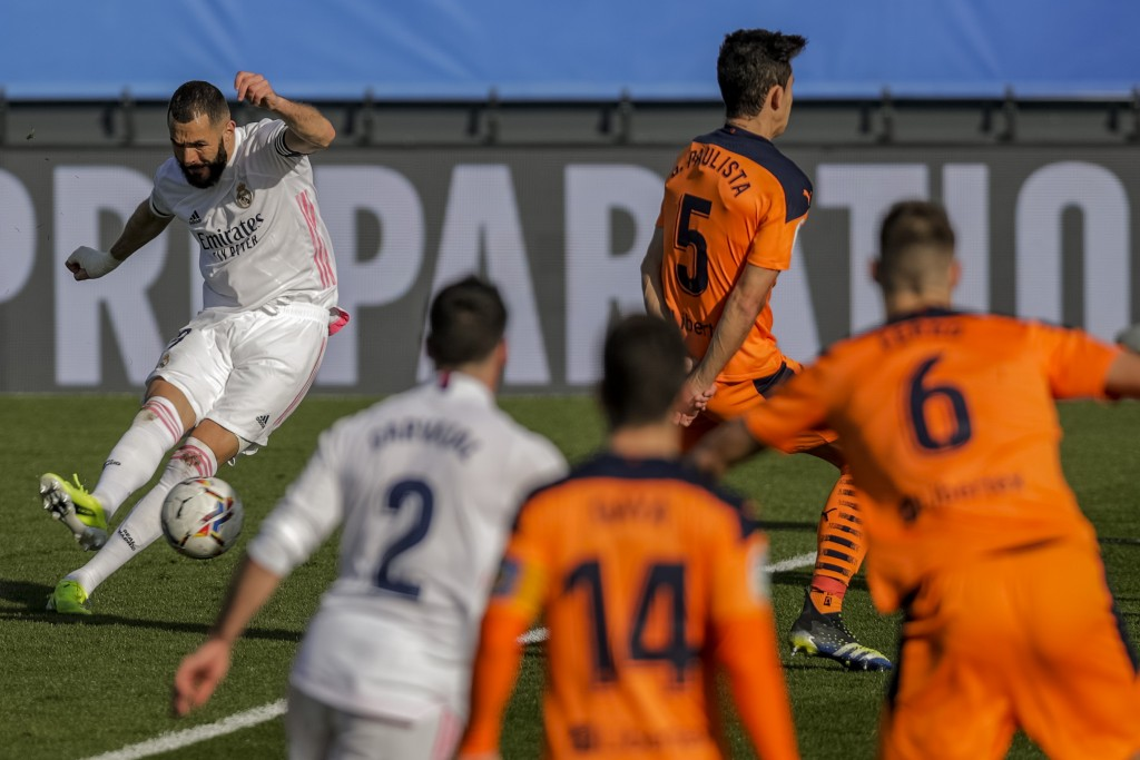 Real Madrid's Karim Benzema shoots to score the opening goal during the Spanish La Liga soccer match between Real Madrid and Valencia at the Alfredo D...
