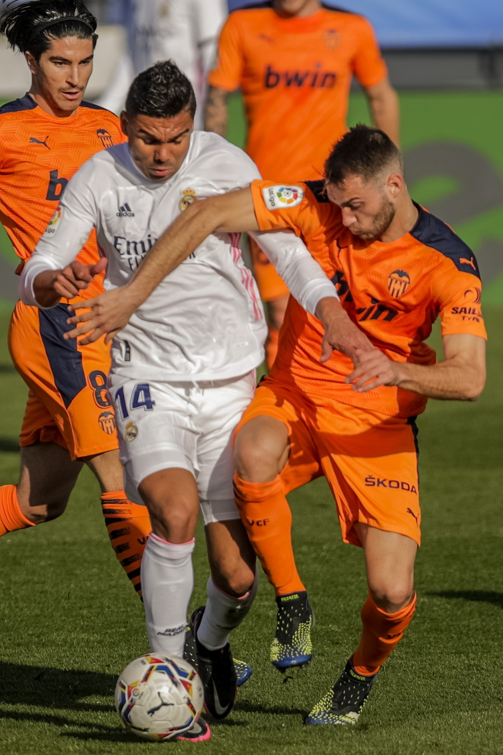 Real Madrid's Casemiro, left, is tackled by Valencia's Ferro during the Spanish La Liga soccer match between Real Madrid and Valencia at the Alfredo D...