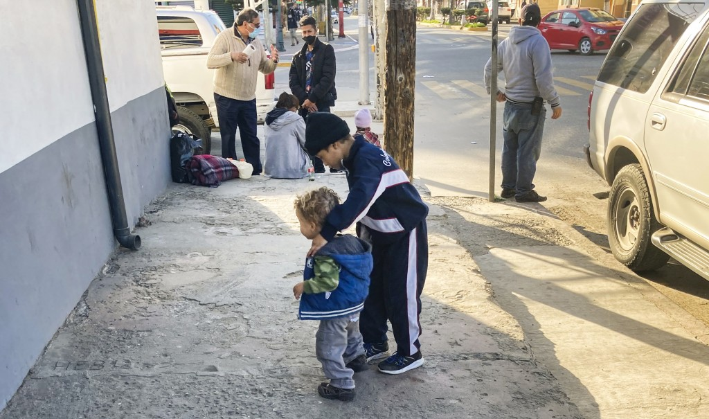 Honduran boys whose family wants to seek asylum in the U.S., play on the sidewalk in Tijuana, Mexico, Monday, Feb. 8, 2021. Thousands of people are wa...