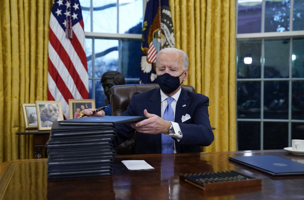 FILE - In this Jan. 20, 2021, file photo, President Joe Biden signs his first executive orders in the Oval Office of the White House in Washington. Th...
