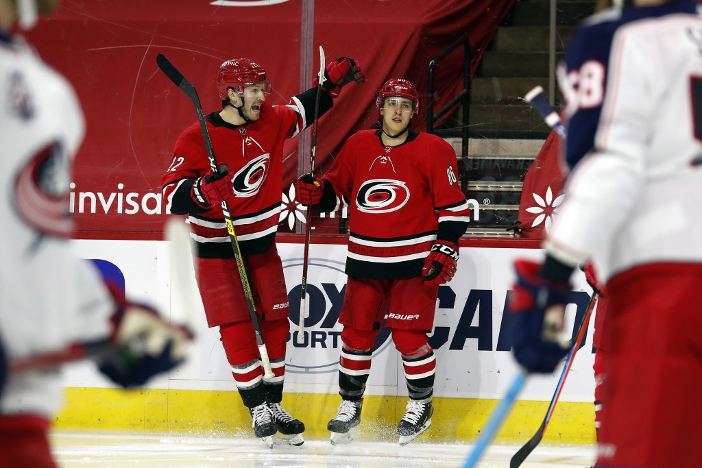 Carolina Hurricanes' Teuvo Teravainen (86) right, celebrates his goal with teammate Brett Pesce (22) during the second period of an NHL hockey game ag...